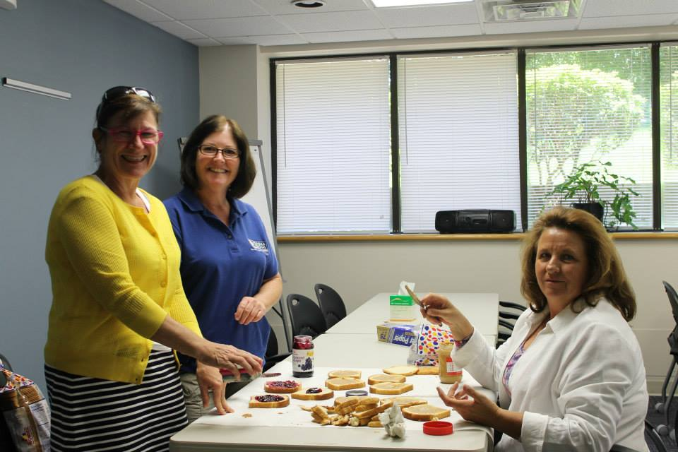 Joan Daugherty, executive director of the Richard A. Henson Cancer Institute, nurse navigator Angie Ness and Mary Rose Custer, a Radiation Oncology nurse, helped make sandwiches for children of survivors attending the event.